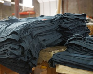 Stacks of grey T-shirts on wooden tables